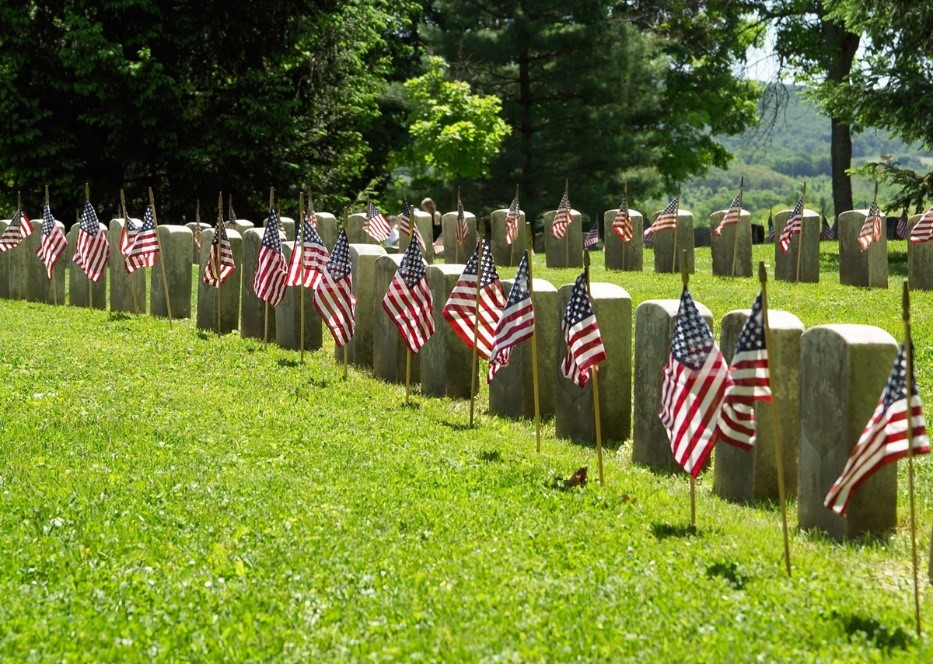 Memorial Day Genealogy by popular US online genealogists, Price Genealogy: image of headstones with American flags in front of them.