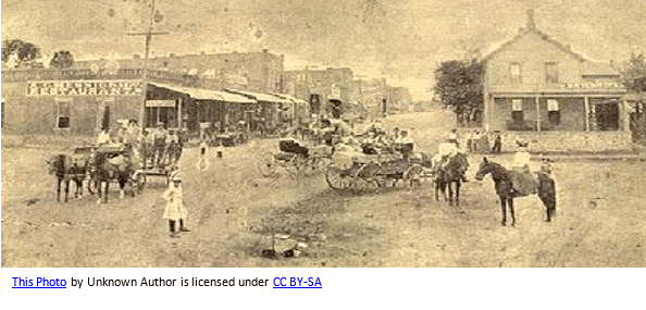Oklahoma Genealogy by popular US online genealogists, Price Genealogy: sepia image of a Oklahoma town with a dirt road, people riding wagons pulled by horses, and some brick and wood slat buildings.