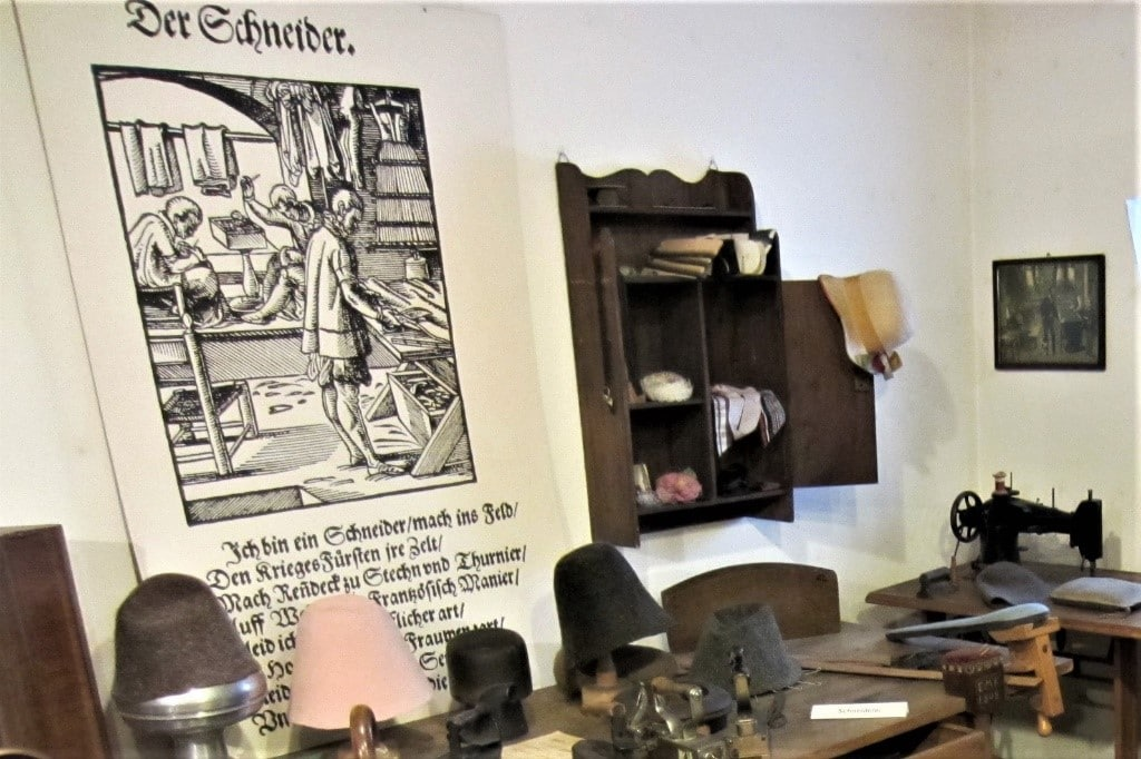 German Naming Customs by popular US online genealogists, Price Genealogy: image of a room decorated with old german hats, a german sign, a desk, and an antique black sewing machine.